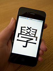 Student using app to learn mandarin Chinese characters on an Apple iphone 4G smart phone