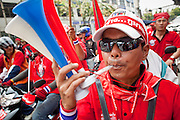 "Mar. 27, 2010 - BANGKOK, THAILAND:  A Red Shirt blows through a noise maker during their march in Bangkok March 27. More than 80,000 members of the United Front of Democracy Against Dictatorship (UDD), also known as the ""Red Shirts"" and their supporters marched through central Bangkok March 27 during a series of protests against and demand the resignation of current Thai Prime Minister Abhisit Vejjajiva and his government. The protest is a continuation of protests the Red Shirts have been holding across Thailand. They support former Prime Minister Thaksin Shinawatra, who was deposed in a coup in 2006 and went into exile rather than go to prison after being convicted on corruption charges. Thaksin is still enormously popular in rural Thailand.    PHOTO BY JACK KURTZ"