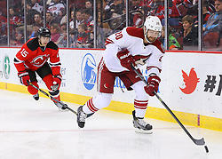 Mar 27, 2014; Newark, NJ, USA; Phoenix Coyotes defenseman Chris Summers (20) plays the puck while being defended by New Jersey Devils left wing Tuomo Ruutu (15) during the first period at Prudential Center.