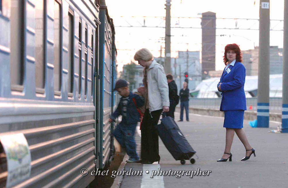 "A ""Provodnitsia"" follows  passengers boarding a Trans-Siberian Railway train for Tomsk, Siberia and beyond, departing the platform at Yarosliavsky Station in Moscow, Russian Federation on Thursday, June 9, 2005."