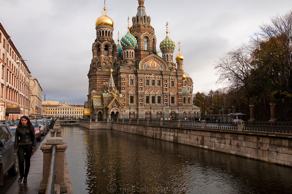 A woman walks on a sidewalk along the edge of the Griebodov Canal outside the Church of our Saviour on the Spilled Blood in St. Petersburg, Russia. (From the book What I Eat: Around the World in 80 Diets.) Suppression and neglect during the Soviet era have bequeathed restoration artists like Vyacheslav Grankovskiy with a lifetime of restoration work.