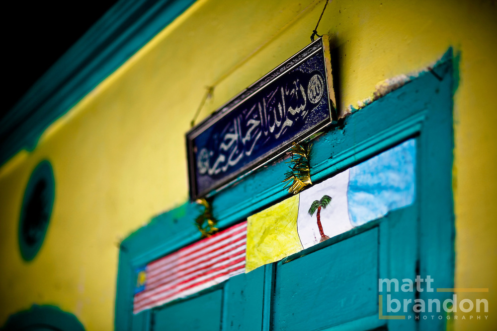 The child's paper flags of Malaysia and the state of Penang rest underneath the Islamic shahada.