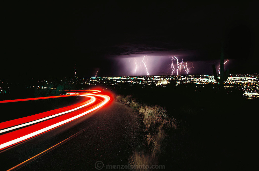 Summer lightning storm over Tucson, Arizona from Tumamoc Hill with Saguaro cactus. Storms erupt regularly during Arizona summers due to the moist air that flows in from the Gulf of California then collides with nearby mountains and is forced upward, where it condenses into thunderclouds. Tucson, Arizona, USA. 1992..