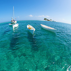 A flotilla of small conch boats used by traditional fisherman at anchor inside to the barrier reef of Belize.