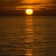 The golden sun drops below the clouds just before hitting the horizon. The very calm waters create a sharp reflection on the water. Taken at Swains Reef on the southern end of the Great Barrier Reef of the coast of Queensland, Australia.
