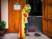 07 APRIL 2017 - BANGKOK, THAILAND:  A boy in a Chinese Lion Dance outfit looks into his friend's home in Pom Mahakan. The final evictions of the remaining families in Pom Mahakan, a slum community in a 19th century fort in Bangkok, have started. City officials are moving the residents out of the fort. NGOs and historic preservation organizations protested the city's action but city officials did not relent and started evicting the remaining families in early March.             PHOTO BY JACK KURTZ