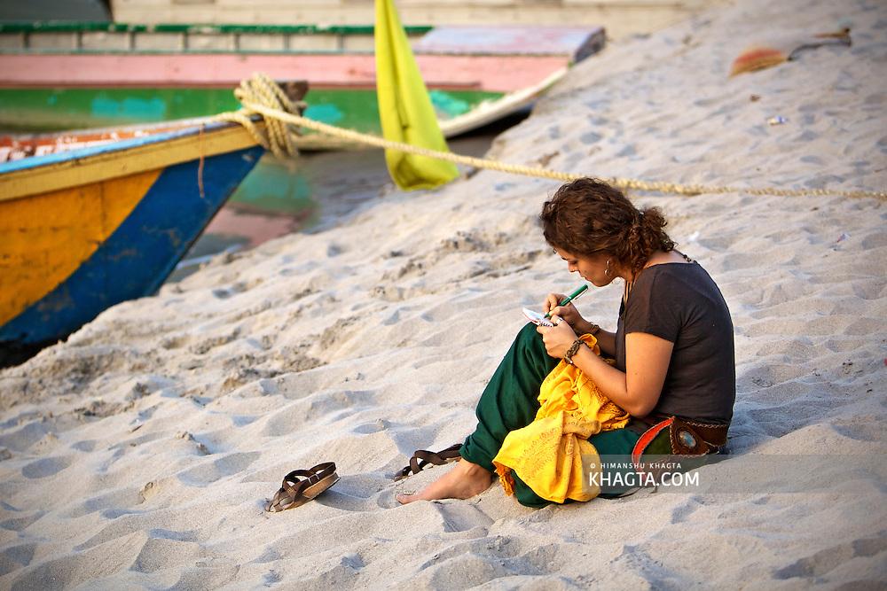A lady writing something on the bank of river Ganga at Laxman Jhula in Rishikesh, Uttarakhand