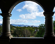 A stone arch in the Centro Cultural Santo Domingo frames a view of the Jardín Etnobotánico and the distant mountains, Oaxaca