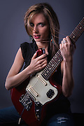 Beautiful woman in a black top with a red Fender Jaguar guitar
