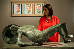 "© Licensed to London News Pictures. 19/06/2015. London, UK. A Sotheby's staff member looks at Henry Moore's bronze,  ""Falling Warrior"" (est. £1.8m - £2.5m), with Francis Bacon's ""Three studies for self-portrait"" (est. £10m-£15m) in the background, at Sotheby's Impressionist, Modern & Contemporary Art preview, ahead of the sale on 24 June 2015. Leading the sale are Kazimir Malevich's, ""Suprematism, 18th Construction"" and Edouard Manet's ""Le Bar aux Folies-Bergère"".  Photo credit : Stephen Chung/LNP"