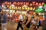 "01 SEPTEMBER 2011 - ST. PAUL, MN:  People walk past a fried cheese curd booth at the Minnesota State Fair. The Minnesota State Fair is one of the largest state fairs in the United States. It's called ""the Great Minnesota Get Together"" and includes numerous agricultural exhibits, a vast midway with rides and games, horse shows and rodeos. Nearly two million people a year visit the fair, which is located in St. Paul.  PHOTO BY JACK KURTZ"