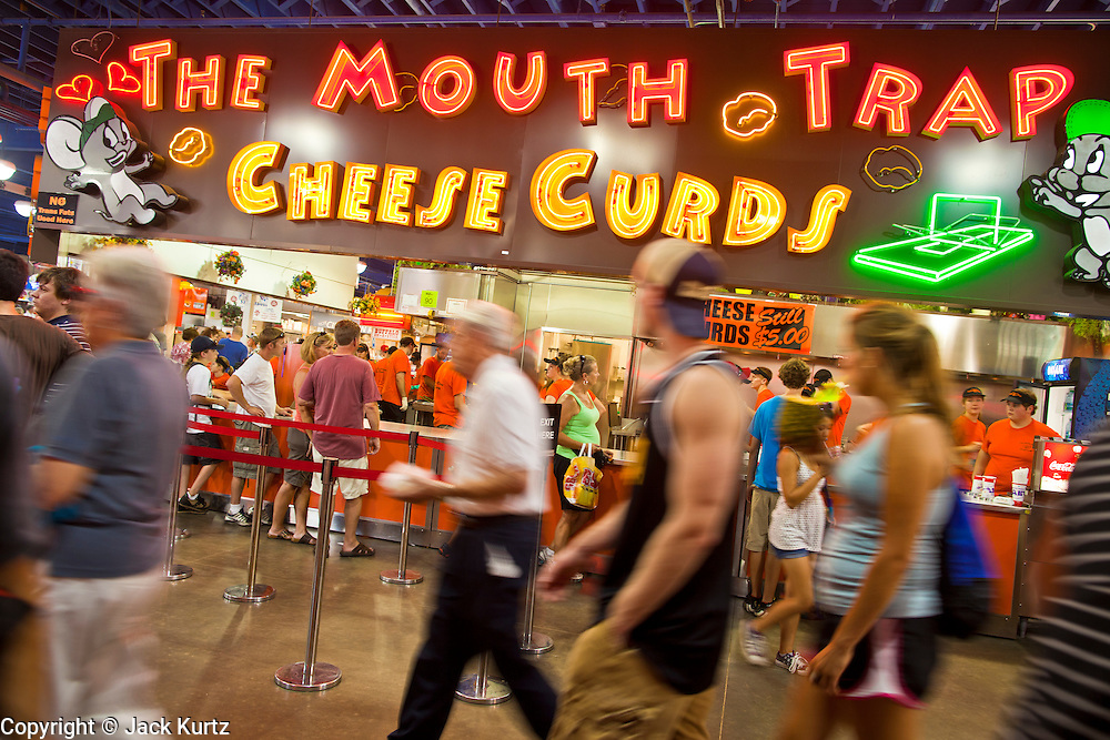 """01 SEPTEMBER 2011 - ST. PAUL, MN:  People walk past a fried cheese curd booth at the Minnesota State Fair. The Minnesota State Fair is one of the largest state fairs in the United States. It's called """"the Great Minnesota Get Together"""" and includes numerous agricultural exhibits, a vast midway with rides and games, horse shows and rodeos. Nearly two million people a year visit the fair, which is located in St. Paul.  PHOTO BY JACK KURTZ"""