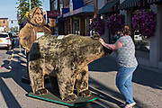 A worker adjusts a giant stuffed bear and Bigfoot display to attract tourists at a shop along 4th Avenue in downtown Anchorage, Alaska.
