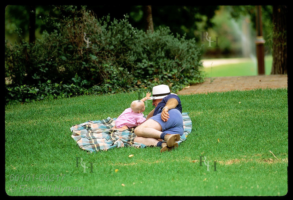 Infant girl tries to grab hat off grandad lying on blanket in public park in Wagga Wagga, NSW. Australia