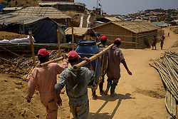 "Sanitation workers employed by the Red Cross carry barrels of waste to the desludging facility in Balukhali camp in CoxÕs Bazar, southern Bangladesh, where human waste is treated with lime and then dried. British aid workers fear they may be cut off from supporting hundreds of thousands of Rohingya refugees once the monsoon season hits the country, after a few hours of rain ""completely transformed"" parts of the camps."