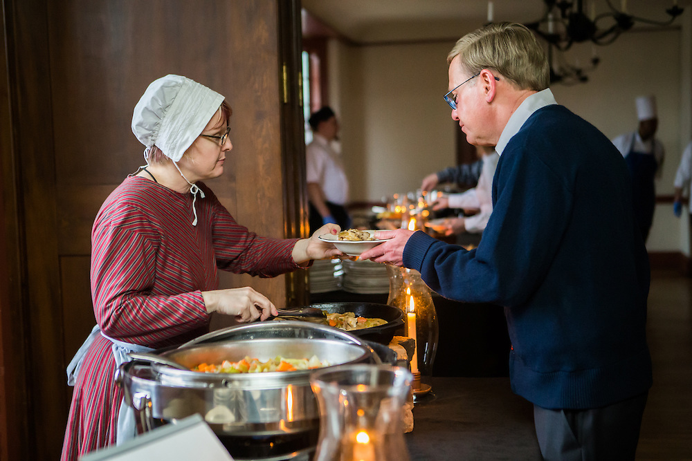 Woman dressed in period clothing serves a man food at a Greenfield Village Eagle Tavern Local Roots dinner. Photographed for The Henry Ford by KMS Photography