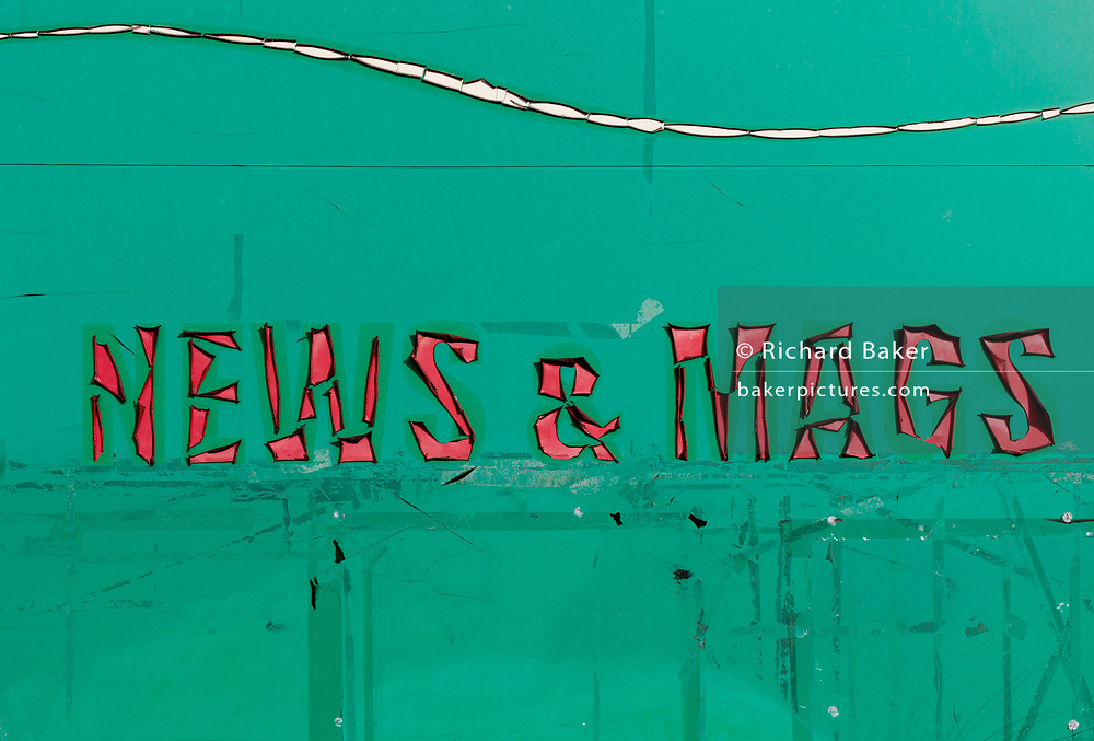 A detail of sun-burned shrivelled lettering outside a local convenience shop and newsagent in East Dulwich, on 10th February 2019, in London, England.