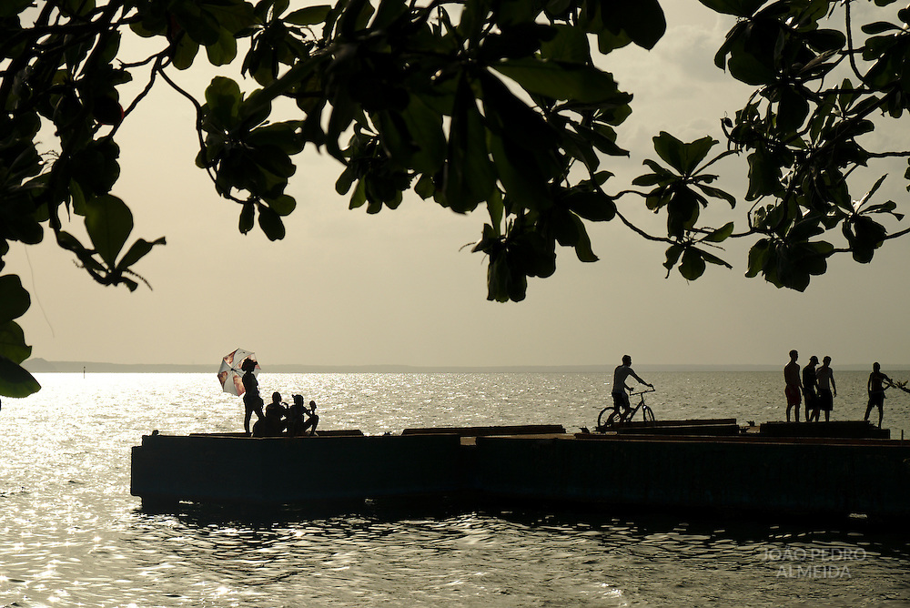 Boys using an abandoned pier close to Cienfuegos marina to dive on a hot Sunday
