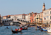 "Gondoliers row gondolas on the Grand Canal at Rialto Bridge (or Ponte di Rialto, built 1591), which is the oldest of four bridges spanning the Grand Canal in Venice, Italy, Europe. The single span stone bridge designed by Antonio da Pontestone is an architectural icon of Venice. In 452 AD, Attila the Hun invaded Italy, and people retreated to offshore islands called Rivo Alto (high bank), or Ri'Alto, the center of Venice. Venice/Venezia is the capital of Italy's Veneto region, named for the ancient Veneti people from the 900s BC. The romantic ""City of Canals"" stretches across 100+ small islands in the marshy Venetian Lagoon along the Adriatic Sea in northeast Italy. The Republic of Venice was a major maritime power during the Middle Ages and Renaissance, a staging area for the Crusades, and a major center of art and commerce (silk, grain and spice trade) from the 1200s to 1600s. The wealthy legacy of Venice stands today in a rich architecture combining Gothic, Byzantine, and Arab styles. Venice and the Venetian Lagoons are on the prestigious UNESCO World Heritage List."
