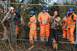 Harefield, UK. 7 February, 2020. Activists lean on Heras fencing being erected by HS2 engineers to surround three environmental activists from Extinction Rebellion who have climbed an ancient tree close to the Harvil Road wildlife protection camp in order to try to protect it from felling. HS2 are expected to try to fell large numbers of mature trees in the immediate vicinity over the weekend even though the high-speed rail link is still awaiting Boris Johnson's approval.