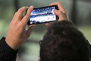 A fan takes a photo of the new rink before an exhibition game at RIT's Gene Polisseni Center on Monday, September 29, 2014.
