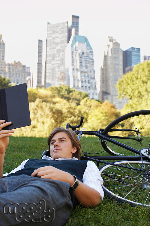 Man lying on lawn reading book