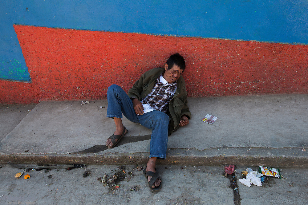 A drunk man lays on the street the day after residents of San Miguel Acatán, highland town made up mostly of Akatek Mayans, celebrated Day of the Dead. A syncretic holiday that blends Catholic Christian beliefs with local mayan customs, Day of the Dead is of high importance in many communities in Guatemala and Mexico. San Miguel Acatán, Huehuetenango, Guatemala. November 3, 2012.