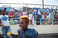 """Family friends came down from the stands to greet Maxwell """"Bunchie"""" Young, 10, at the fence after his game. He and his dad Dave Young, left, share a laugh, as they're both fixture on the football fields in South L.A."""