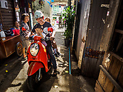 16 MAY 2017 - BANGKOK, THAILAND: LEK, a community leader in Pom Mahakan brings some of the community children home from his school on his motorbike. The final evictions of the remaining families in Pom Mahakan, a slum community in a 19th century fort in Bangkok, have started. City officials are moving the residents out of the fort. NGOs and historic preservation organizations protested the city's action but city officials did not relent and started evicting the remaining families in early March.           PHOTO BY JACK KURTZ