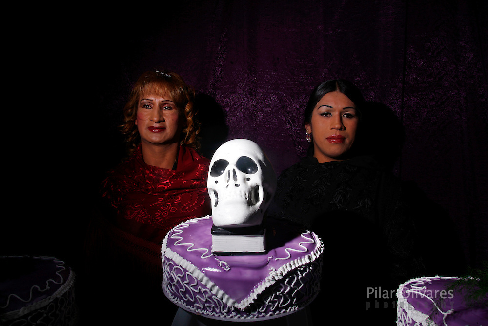 Transvestites Carla (L) and Iris pose with a skull as they celebrate the Day of Skulls in La Paz November 8, 2009. Bolivians who keep close relatives' skulls at home as a macabre talisman flock to the cemetery chapel once a year to have the craniums blessed and to bring themselves good luck in the future.