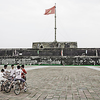 HUE, VIETNAM - AUGUST 2, INDEPENDENCE DAY: Vietnamese boys lingering in front of the Flag Tower overlooking Ngo Mon Square in Hue, on Vietnam's national day, August 2, 2010.