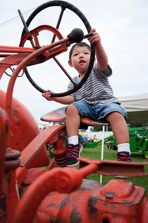 Holden Miller, 2, checks out one of many tractors on display at the farm implement show at the Walworth County Fair in Elkhorn, Wis., on Sept. 6, 2009.