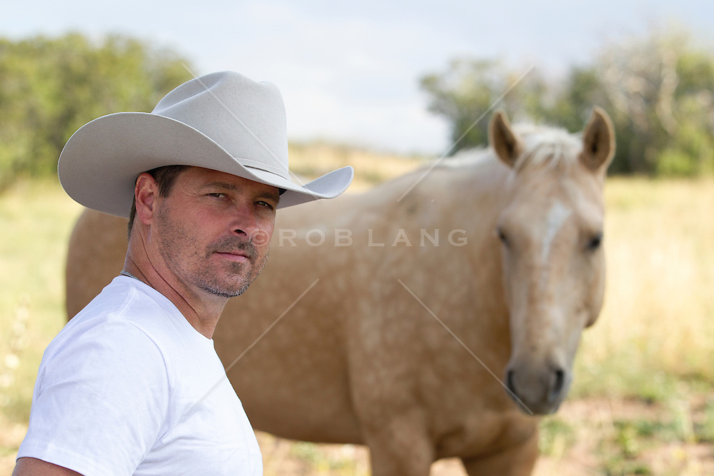 handsome cowboy standing by a horse in New Mexico