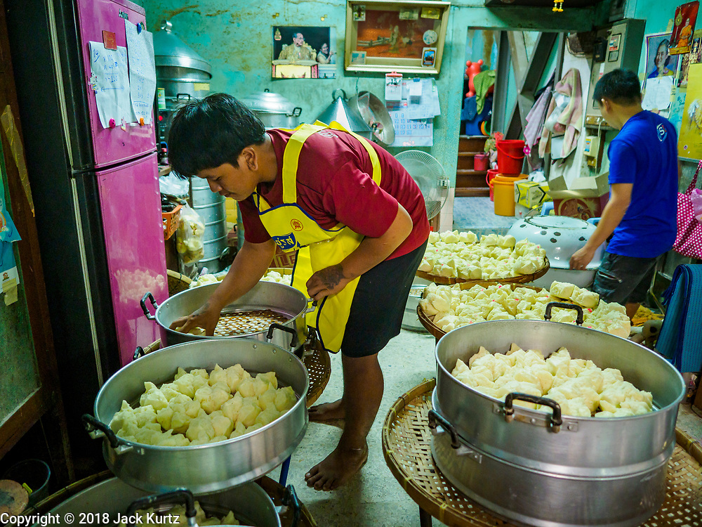 "12 FEBRUARY 2018 - BANGKOK, THAILAND:  Men set out freshly steamed buns in a home that makes steamed Chinese buns, called ""bao"" in the Chinatown neighborhood of Bangkok. Bao are eaten at midnight on the Lunar New Year and served to guests during New Year's entertaining. Lunar New Year, also called Tet or Chinese New Year, is 16 February this year. The coming year will be the Year of the Dog. Thailand has a large Chinese community and Lunar New Year is widely celebrated in Thailand, especially in Bangkok and large cities with significant Chinese communities.   PHOTO BY JACK KURTZ"