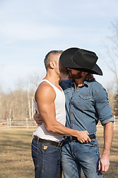 cowboy kissing another man outdoors