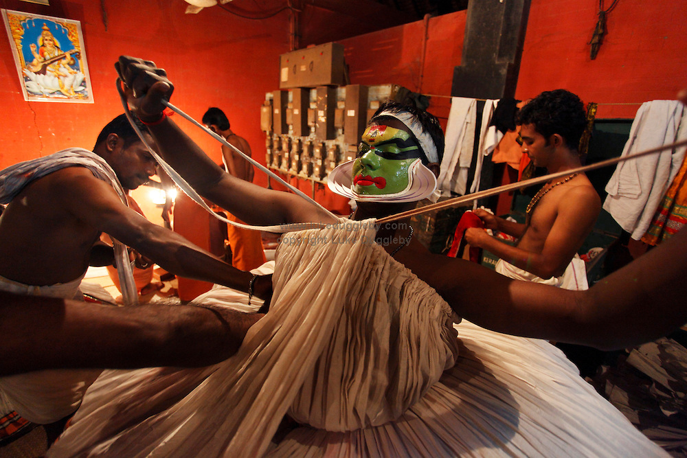 A student gets 'wound' into the Kathakali costume in the back room of the Kuttambalam. Recently renamed the Kalamandalam Deemed University of Arts and Culture but better known by its original name Kerala Kalamandalam it is one of India's most prestigious performing arts schools of which the art of Kathakali is the most renowned discipline. Founded in 1930 by poet and performer Vallathol Narayana Menon and Manakkulam Mukunda Raja who at a time of British Colonial domination feared that the support of local landlords whom held patronage over the arts often employing their own troupes would diminish decided to open the school to guarantee the continuation of the art. 80 years later and with over 500 students and 70 teachers the now turned University of 3 years still trains students in highly stylized classical Indian dance-drama, musical instruments and make-up..Kathakali originated in the present day State of Kerala around the 17th century and whilst having been adapted and modernised throughout history remains an intricate part of Keralan culture in telling ancient Hindu epics. In the local dialect of Malayalam, the word 'Katha' means story and 'Kali' means play.