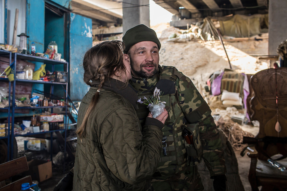 PERVOMAISKE, UKRAINE - MARCH 20, 2015: Volodya, a fighter for the Dnipro-1 battalion, a pro-Ukrainian militia, receives a kiss from his wife Natalia after bringing her flowers picked near the front lines at one of the group's bases known as The Bridge near ongoing battles for the town of Pisky in Pervomaiske, Ukraine. CREDIT: Brendan Hoffman for The New York Times