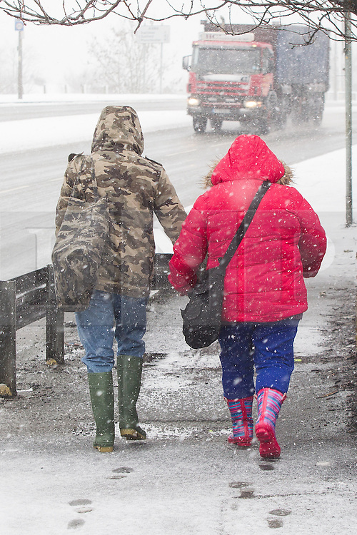 © Licensed to London News Pictures . 05/02/2013 . Manchester , UK . Two women hold hands as they walk carefully along the icy pavements in Swinton , Manchester . Heavy snow is causing traffic delays and accidents on the roads in and around Manchester . Photo credit : Joel Goodman/LNP