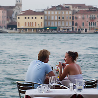A couple enjoys the evening next to a canal on the day the Italian Government and Heath Ministry has issued several warning for the current heath wave