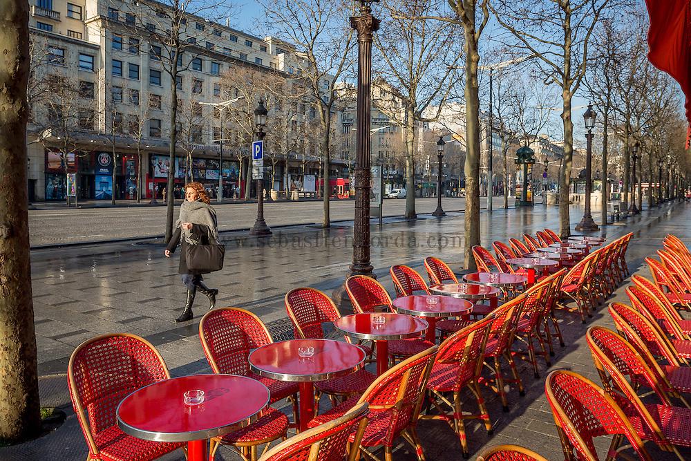 Femme marchant sur les Champs- Elysées devant une terrasse de café // Woman walking on avenue des Champs Elysées in front of a pavment cafe