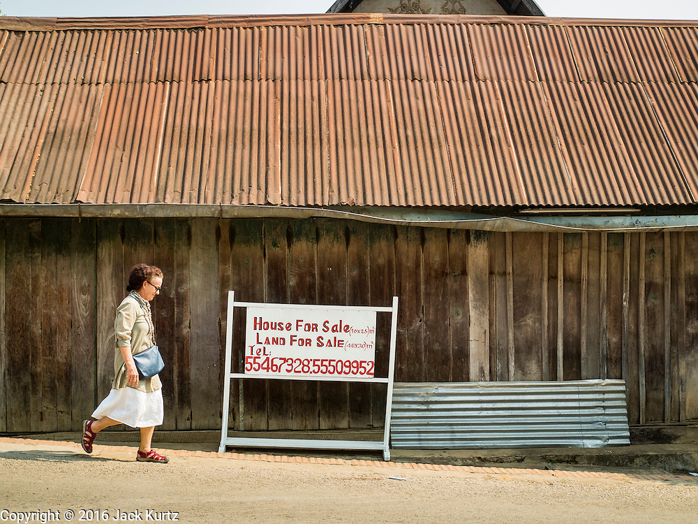 """13 MARCH 2016 - LUANG PRABANG, LAOS: Tourists walk past a home for sale in Luang Prabang. The for sale sign being in English indicates who the property is being marketed to. Luang Prabang was named a UNESCO World Heritage Site in 1995. The move saved the city's colonial architecture but the explosion of mass tourism has taken a toll on the city's soul. According to one recent study, a small plot of land that sold for $8,000 three years ago now goes for $120,000. Many longtime residents are selling their homes and moving to small developments around the city. The old homes are then converted to guesthouses, restaurants and spas. The city is famous for the morning """"tak bat,"""" or monks' morning alms rounds. Every morning hundreds of Buddhist monks come out before dawn and walk in a silent procession through the city accepting alms from residents. Now, most of the people presenting alms to the monks are tourists, since so many Lao people have moved outside of the city center. About 50,000 people are thought to live in the Luang Prabang area, the city received more than 530,000 tourists in 2014.    PHOTO BY JACK KURTZ"""