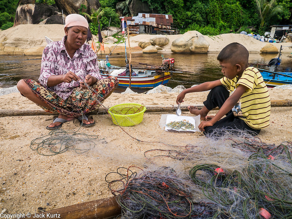 04 NOVEMBER 2012 - KAO SENG, SONGKHLA, THAILAND:  A woman repairs her family's fishing nets while her son finished his breakfast in Kao Seng. Kao Seng is a traditional Muslim fishing village on the Gulf of Siam near the town of Songkhla, in the province of Songkhla. In general, their boats go about 4AM and come back in about 9AM. Sometimes the small boats are kept in port because of heavy seas or bad storms.    PHOTO BY JACK KURTZ