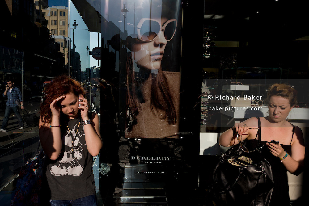 Young women use their smartphones beneath a poster girl for Burberry sunglasses they call Eyewear, in a sunlit London street. Burberry Group plc is a British luxury fashion house, manufacturing clothing, fragrance, and fashion accessories.