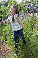 Girl (5-6) standing in garden