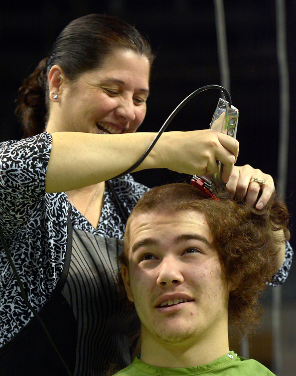 gbs031217g/RIO-WEST -- Jared Bradshaw, 18, a Cleveland High School student, has his mother, Heather Tomlinson, cut off his hair during the New Mexico Firefighters Event for the St. Baldrick's Foundation which raises money for childhood cancer research at the Santa Ana Star Center on  Sunday, March 12, 2017.  Bradshaw had been growing out his hair since last July specially for the fundraiser. (Greg Sorber/Albuquerque Journal)