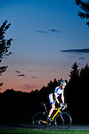 Cyclist at night on a countryside road.