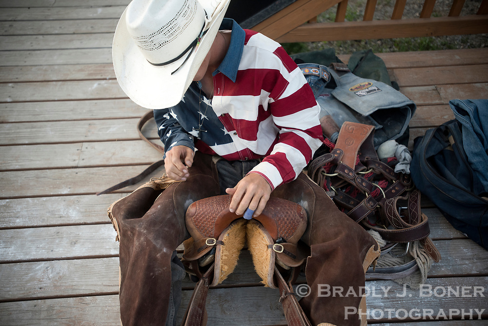 A saddle bronc competitor prepares for his ride during the Jackson Hole Rodeo on the Fourth of July.
