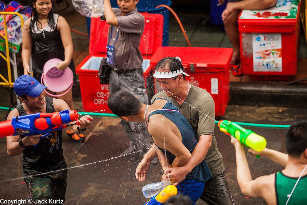 13 APRIL 2014 - BANGKOK, THAILAND:  Tourists in a water fight on Khao San Road, Bangkok's backpacker district, during Songkran. Songkran is celebrated in Thailand as the traditional New Year's Day from 13 to 16 April. Songkran is in the hottest time of the year in Thailand, at the end of the dry season and provides an excuse for people to cool off in friendly water fights that take place throughout the country. Songkran has been a national holiday since 1940, when Thailand moved the first day of the year to January 1.   PHOTO BY JACK KURTZ