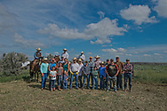 Rancher, John L. Moore, with crew of family and neighbors, cattle branding, corrals on Dead Man Creek, Lazy TL Ranch, north of Miles City, Montana