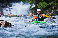 Portrait of a man kayaking down a series of small waterfalls, Snoqualmie River (south fork), Washington, USA. Fall in the wall area.